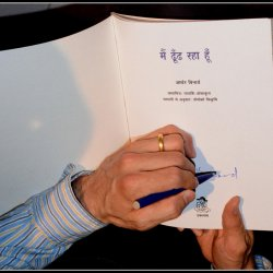 Poet Arthur Binard signing a copy of his book Main Dhoondh Raha Hoon